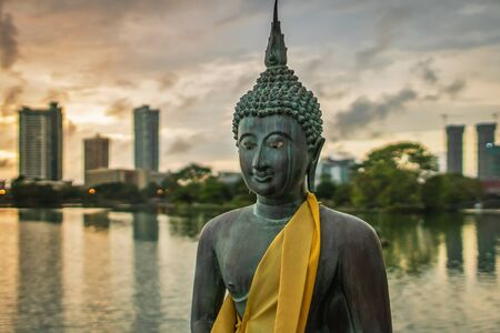 Statue of Buddha made of bronze in a peacefull pose, in front of a cityscape on the Beira Lake in Colombo, Sri Lanka.