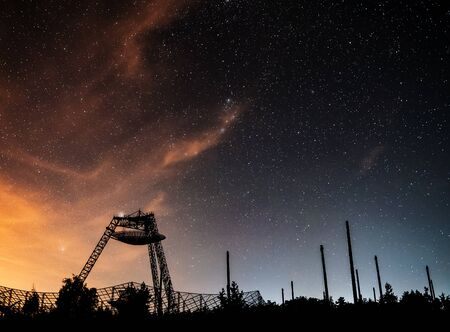 Antenna of the station of exploration of an ionosphere. A silhouette against the background of the night sky with glow, clouds and stars.