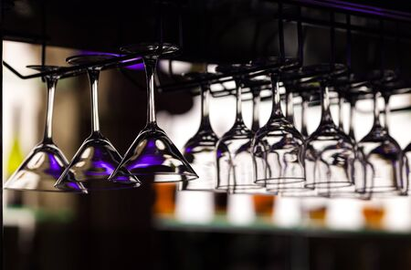 Glasses for martini and wine hang over a bar counter at restaurant, against the background of the shelf with indistinct outlines of bottles.