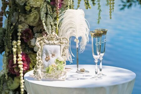 Wedding composition: arch of flowers, table, champagne glasses, pen, solemn frame with gold wedding rings.