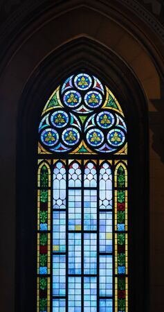 A high stained glass window with colored accents in an old Catholic church.