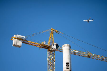 A construction crane erects a tall tower, a civilian passenger plane flies on back of them.