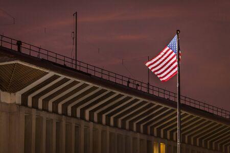 Die US-Flagge weht im Wind vor der US-Botschaft in Sri Lanka, im Vordergrund dunkler Wolken bei Sonnenuntergang.