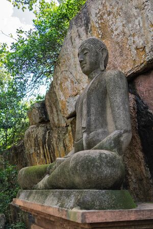 Buddha statue sitting in meditative calm, in the lotus position. It is made of concrete in a classical style, near a stone wall on Sri Lanka.