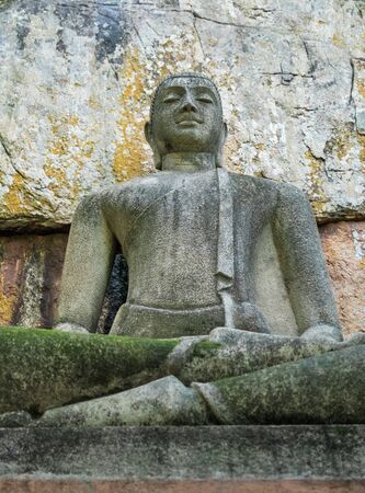 Buddha statue sitting in meditative calm, in the lotus position. It is made of concrete in a classical style, near a stone wall in the thicket of the jungle, in Sri Lanka.