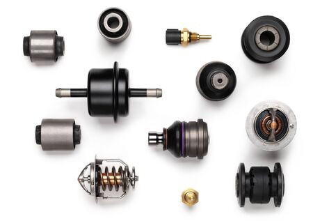 Studio photography - a lot of automotive parts: silent blocks, thermostats, filter, sensors, ball bearings, lie in straight rows on a flat surface isolated on a white background.
