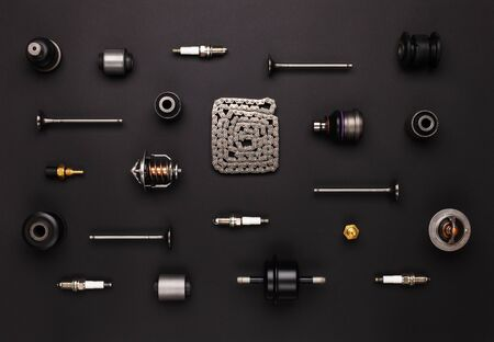 Studio photography - a lot of automotive parts: valves, spark plugs, silent blocks, thermostats, filter, sensors, chain, ball bearings, lie in straight rows on a flat surface isolated on a black background.