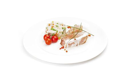 Pieces of fish fillet, light fried and served on a white dish, with garnish of  cherry tomatoes, and rice with vegetables. Isolated on white background.  Banco de Imagens