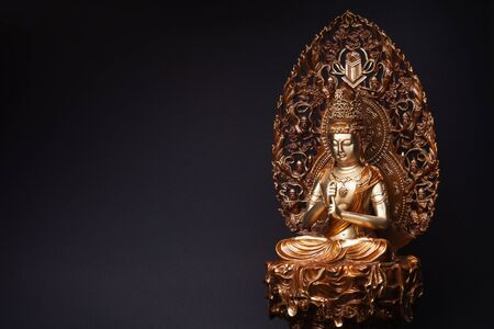 Statue of bronze of Bodhisattva Guan Yin (Avalokiteshvara) sitting in the lotus position, having put hands in knowledge-mudra. Stock Photo