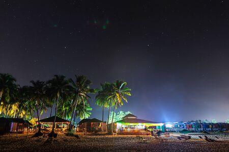 Goan coastal cafes, and beach lodges, in night illumination under the palms and star sky.