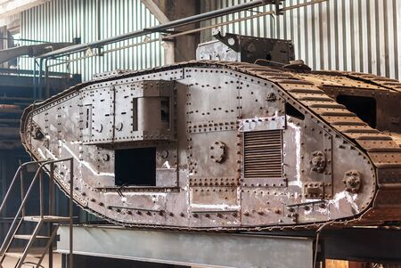 English heavy tank Mark V, of the times of the first world war, in the factory workshop for restoration work. The paint coating is completely removed, polished welding spots are visible.