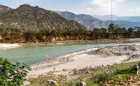 The communist red flag of the Soviet Union flies in the wind on the banks of a mountain river in the background of a valley somewhere in the Himalayas, Nepal.