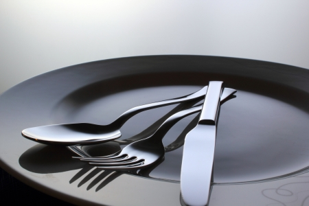 cuchillo de cocina: Plata Tenedor, cuchillo y cuchara en un plato Foto de archivo