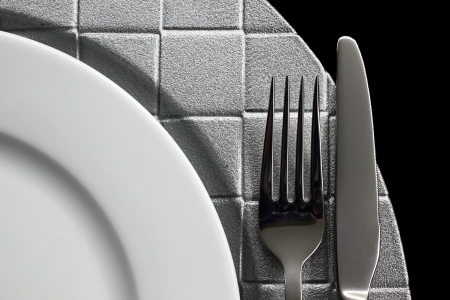 Cutlery and dish on black background photo