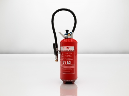 Extinguisher on white and glossy surface photo
