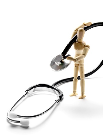 Wooden mannequin holding a stethoscope photo