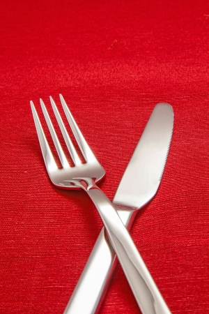 Silver Fork and knife on red table cloth photo