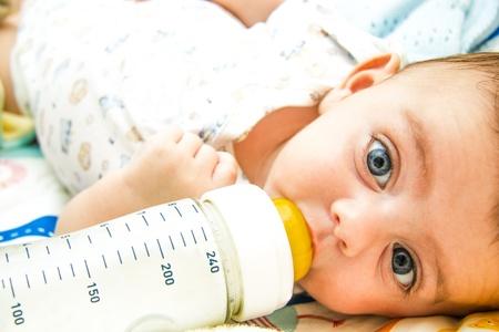 Lovely baby feeding on milk bottle Imagens