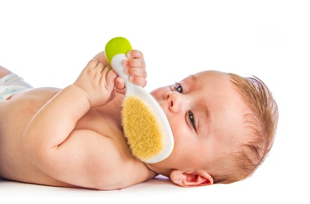 hair brush: Cute baby holding an hairbrush on white