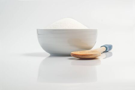 Bowl filled with sugar in white reflective surface photo