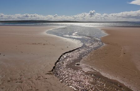 Dunnet Bay is a sand and shingle rural beach backed by some grass covered dunes.This photo shows a trickle flow, which leads to the sea