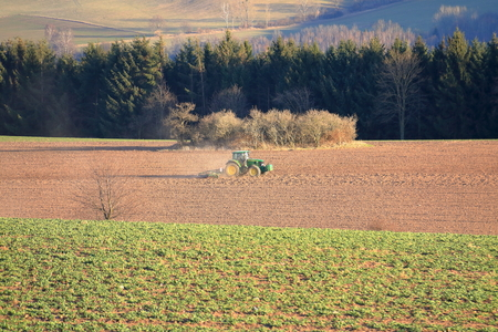 Tractor working on the farm, a modern agricultural transport, a farmer working in the field, fertile land, tractor on sunset background, cultivation of land, agricultural machine