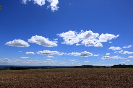 Plowed or Ploughed Field in Countryside and Blue Sky with Clouds over the Horizon