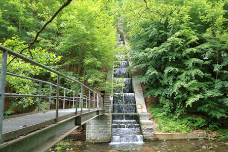 mountain river in the forest with a waterfall and concrete wall near Dresden