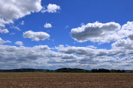 Plowed or Plowed Field in Countryside and Blue Sky with Clouds over the Horizon