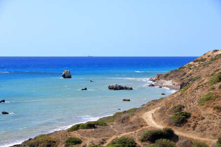 Aphrodite Beach with Stone Rocks in Aphrodite bay of Mediterranean sea water, blue sky in sunny day background, Petra tu Romiou in Cyprus