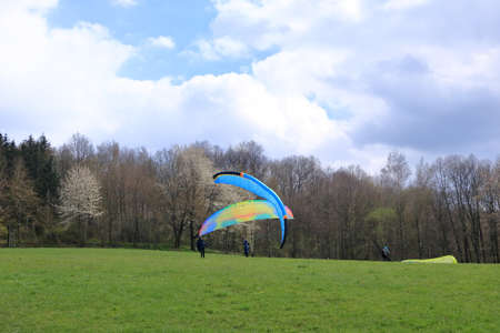 April 25 2021 - Dresden in Germany: Paragliders taking off in front of a green hill