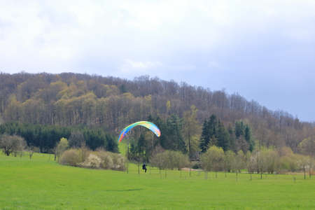 April 25 2021 - Dresden in Germany: Paragliders are landing in front of a green hill
