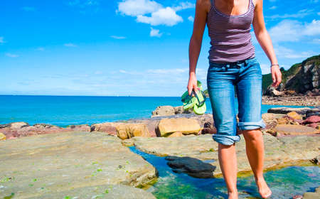 a woman standing on a rock, with the sea as background Stock Photo