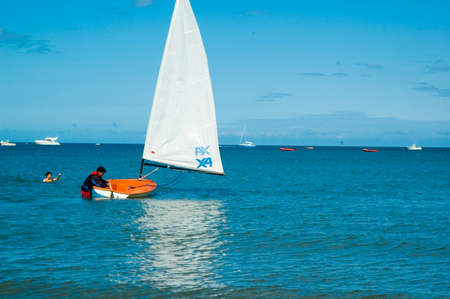 a young boy getting into his sailing boat