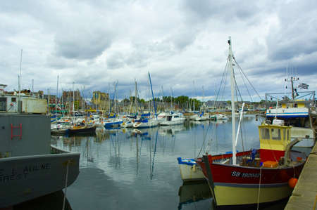 a small harbor with dark stormy clouds above Stock Photo