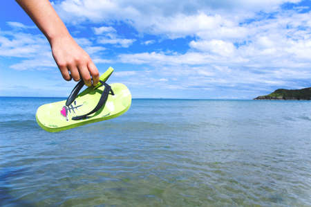 holding a pair of slippers, with the sea as background Stock Photo - 2796550