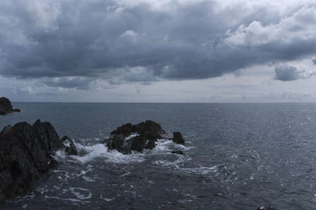 a storm forming over the sea, approaching a rocky coast