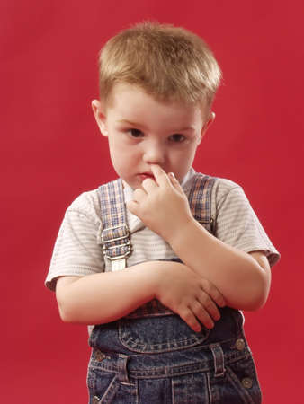 bashfulness: kid of 3-4 years is scratched a finger in a nose Stock Photo