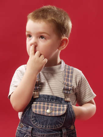 kid of 3-4 years is scratched a finger in a nose  Stock Photo