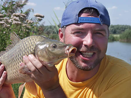happy fisherman has under the thumb a catch is sazan, carp       Stock Photo