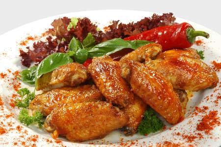 thighs: alas de pollo frito en friture con pimiento rojo Foto de archivo