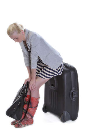expects: Young adult woman with luggagea expects a trip
