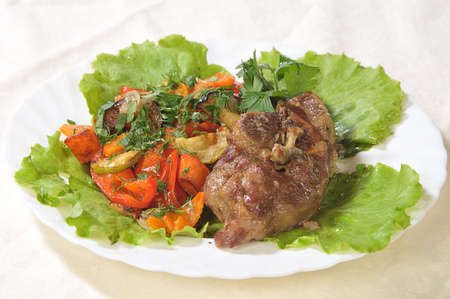 hot dish of a bird with green-stuffs and greenery on a white dish