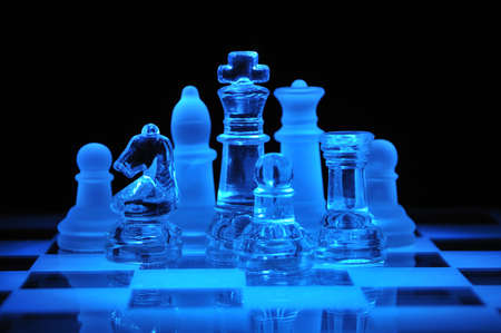 Glass chess figures on the chess field in a dark Stock Photo