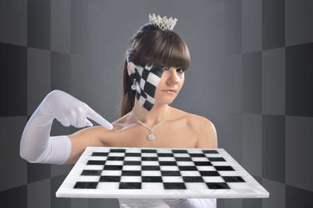 The girl in the image of the chess queen points to the chessboard