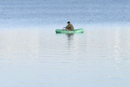 within: Fisherman within green rubber boat in a lake
