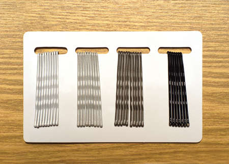 Four group hairpins on white template over brown wood background