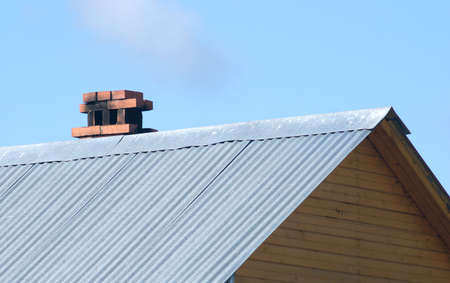 rustproof: Top of country wooden house with rustproof roof and brick smokestack