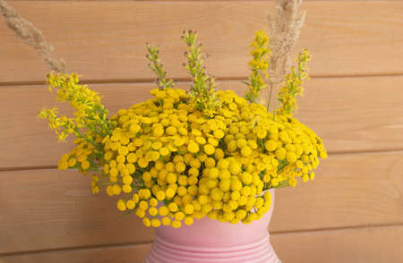 Tansy flowers bouquet in pink vase before wooden house wall
