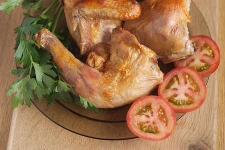 Roast chicken parts with sliced tomatoes and fresh herbs on plate photo